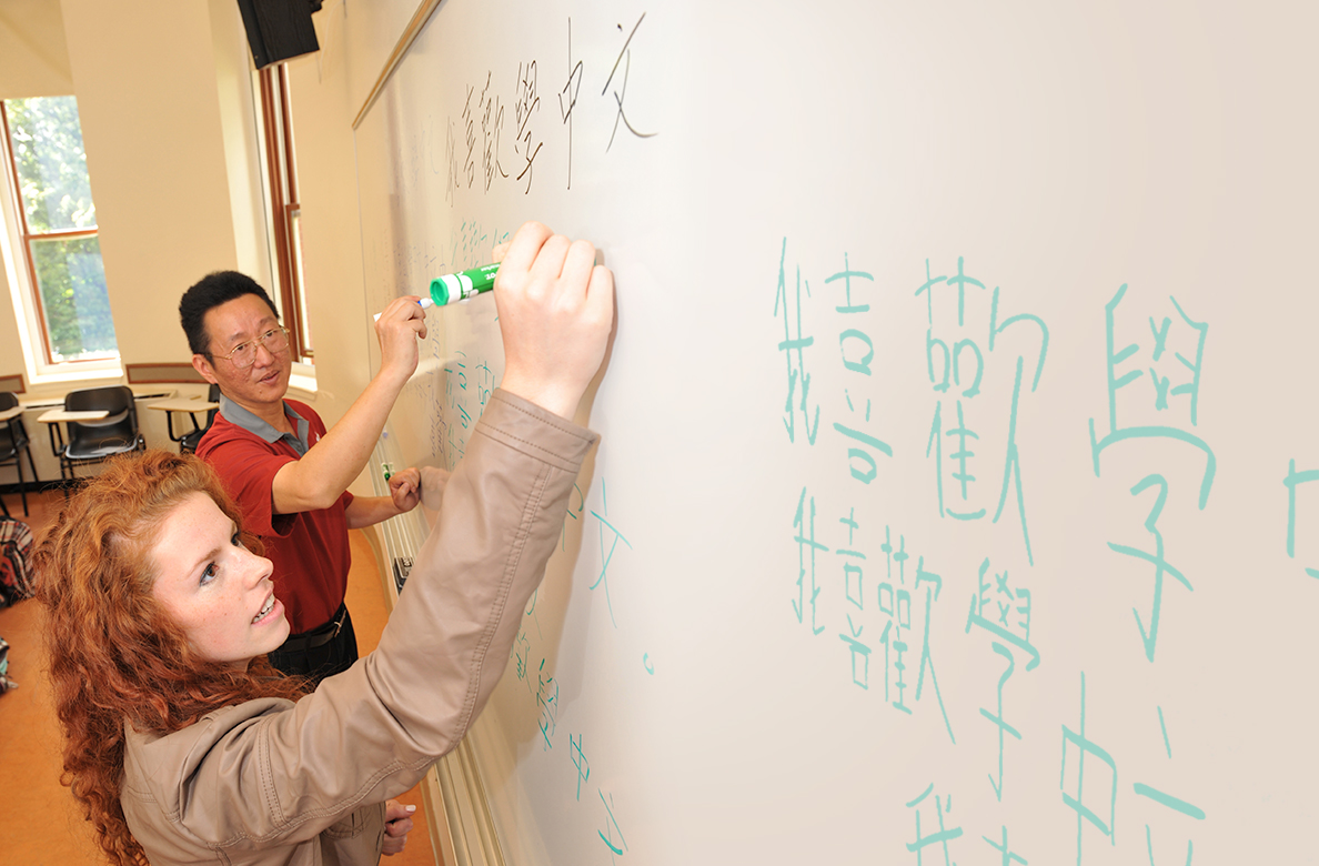 A man and woman practicing Japanese handwriting on a white board