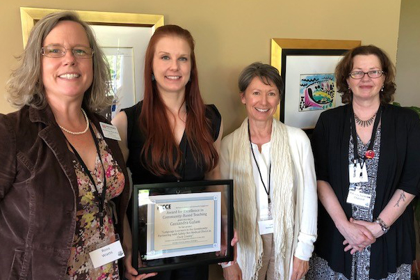 four women, one with a plaque