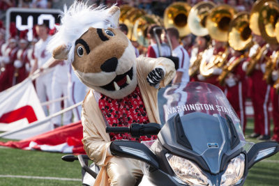 Butch T. Cougar on a motorcycle at football game