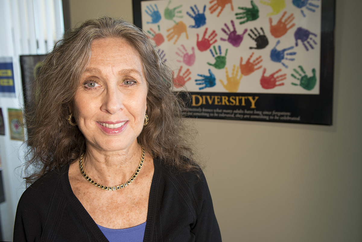 Closeup of Dedra Buchwald, MD, in front of a poster promoting diversity.
