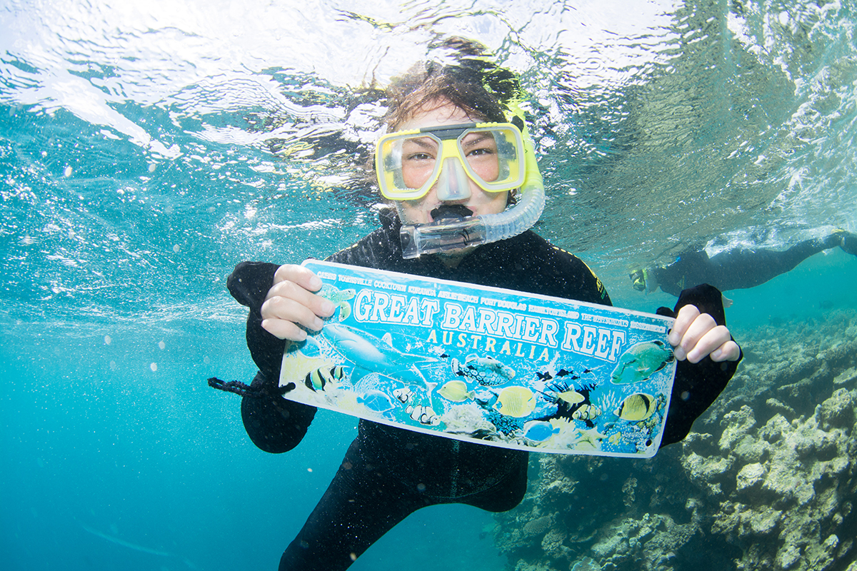 Johnson snorkeling and holding sign underwater that reads 'Great Barrier Reef'.