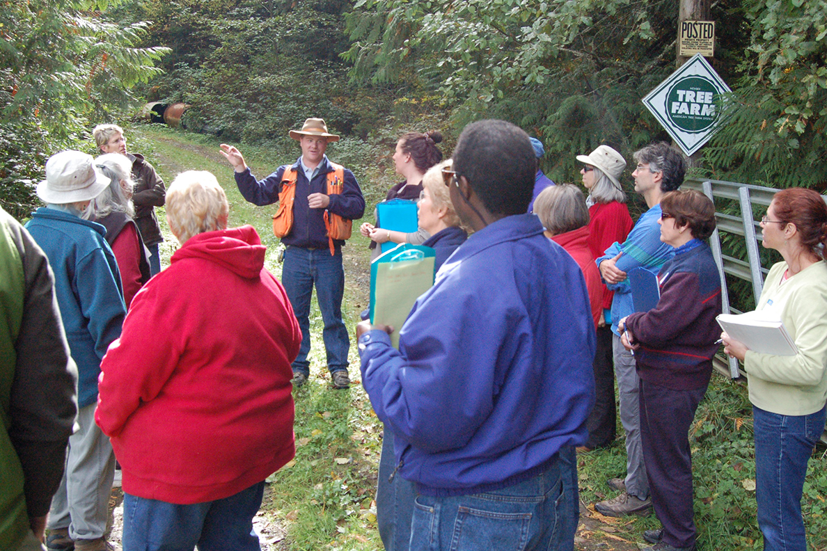 WSU forester speaking to large group of people at a tree farm.