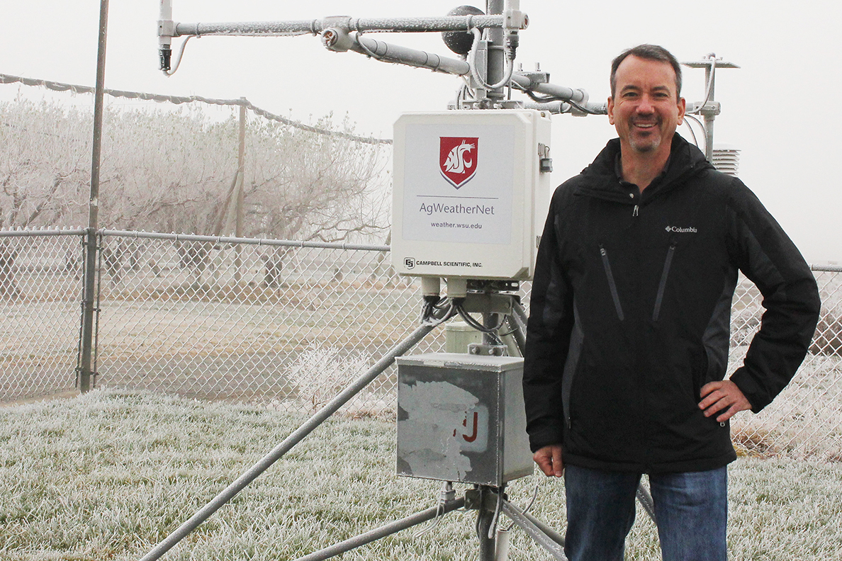 Brown standing in front of AgWeatherNet field equipment.
