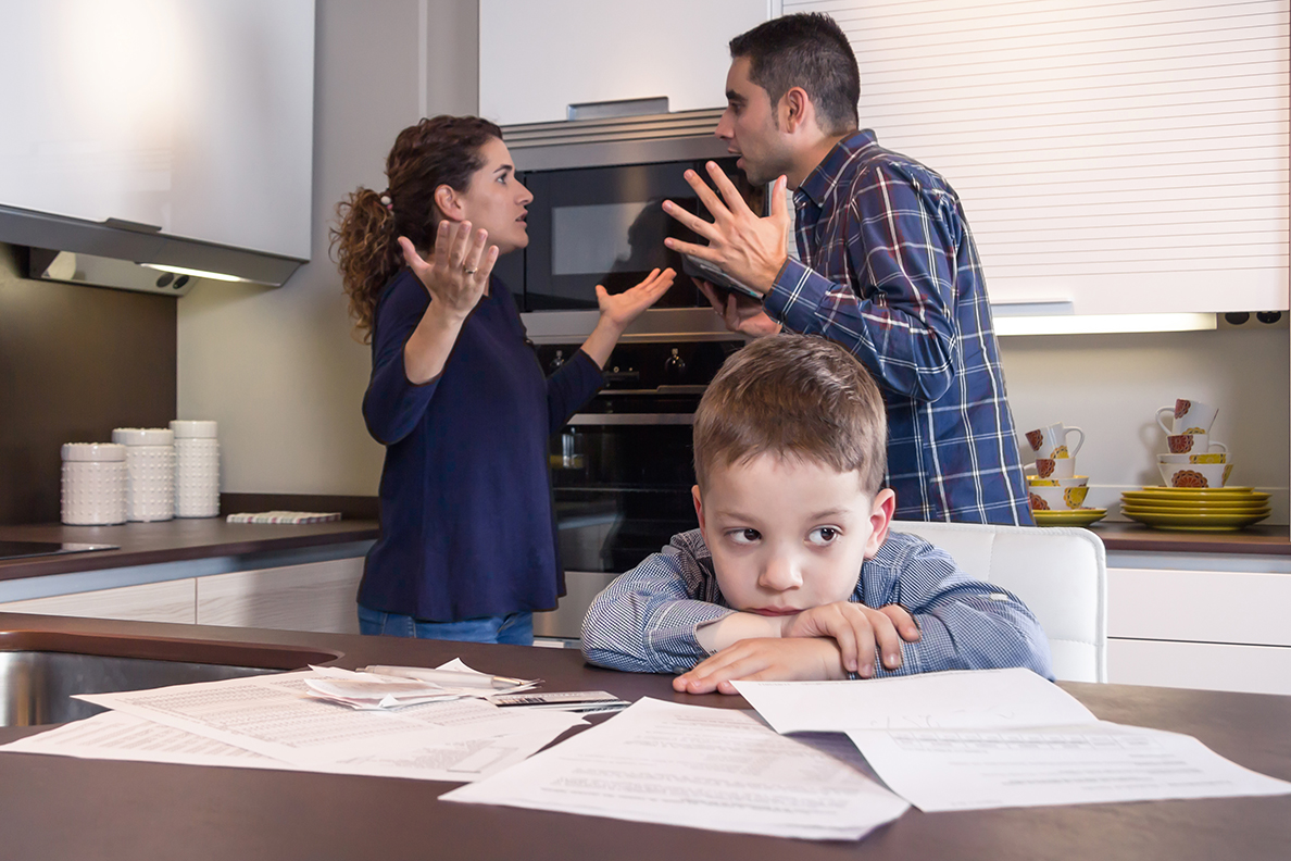 Young boy sitting at kitchen table while parents argue behind him.