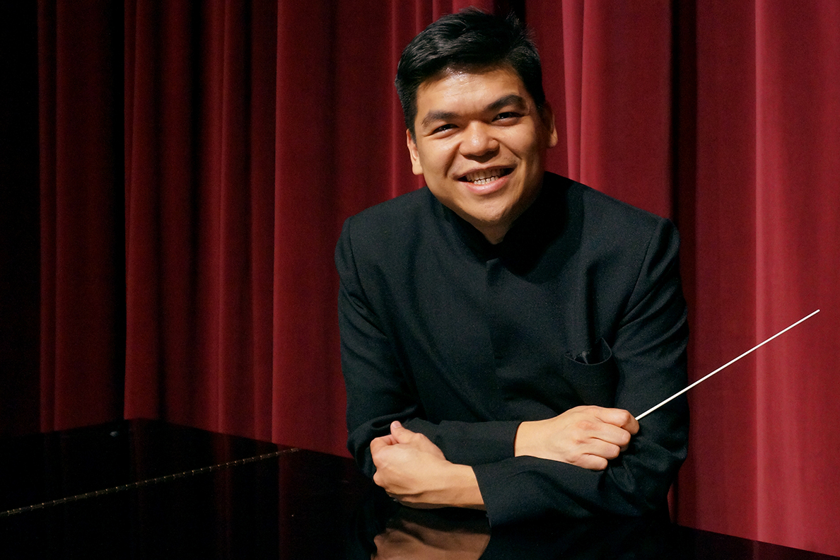 Closeup of Pham leaning against piano with baton in hand.