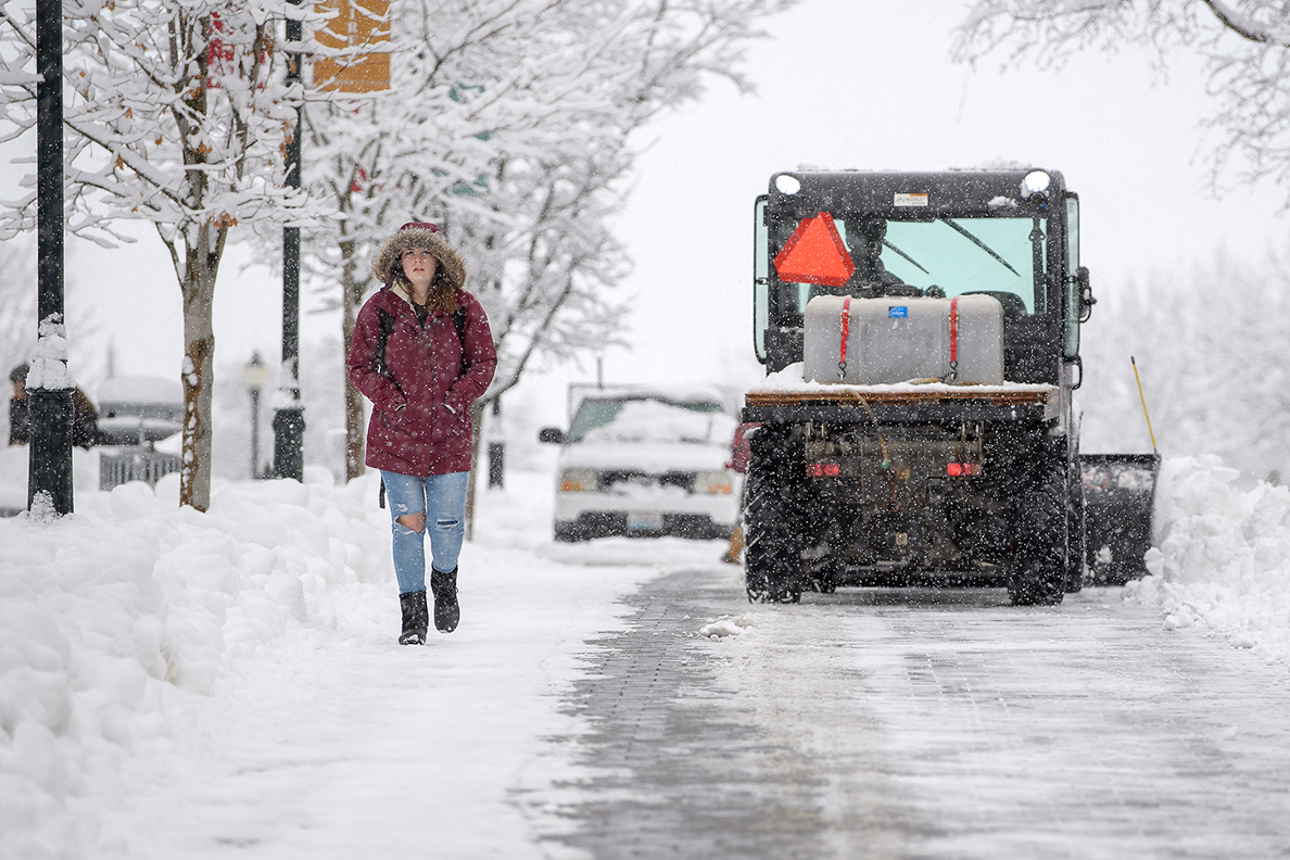 Student walking past large snow removal equipment on WSU Pullman sidewalk.