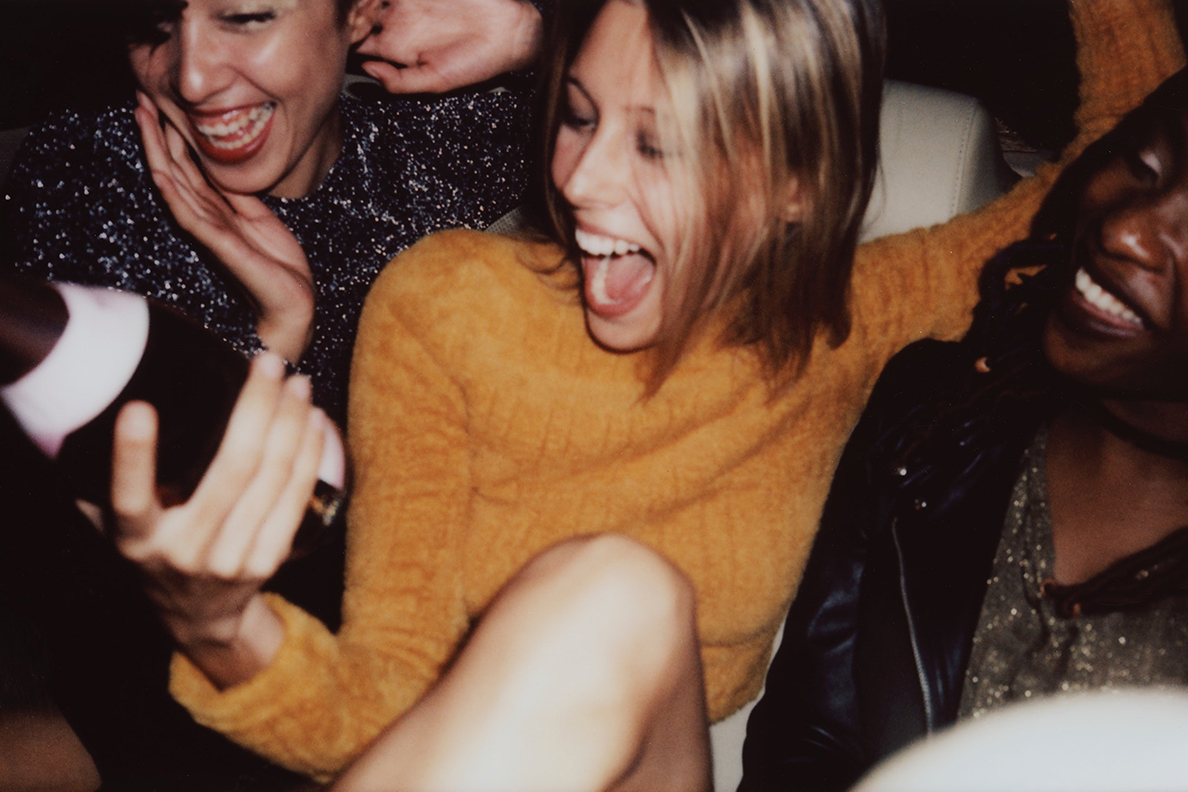 Young women laughing at a party while holding a bottle of alcohol.