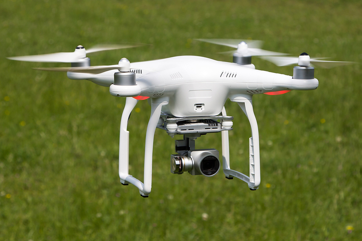 Drone with mounted camera hovering over a field.