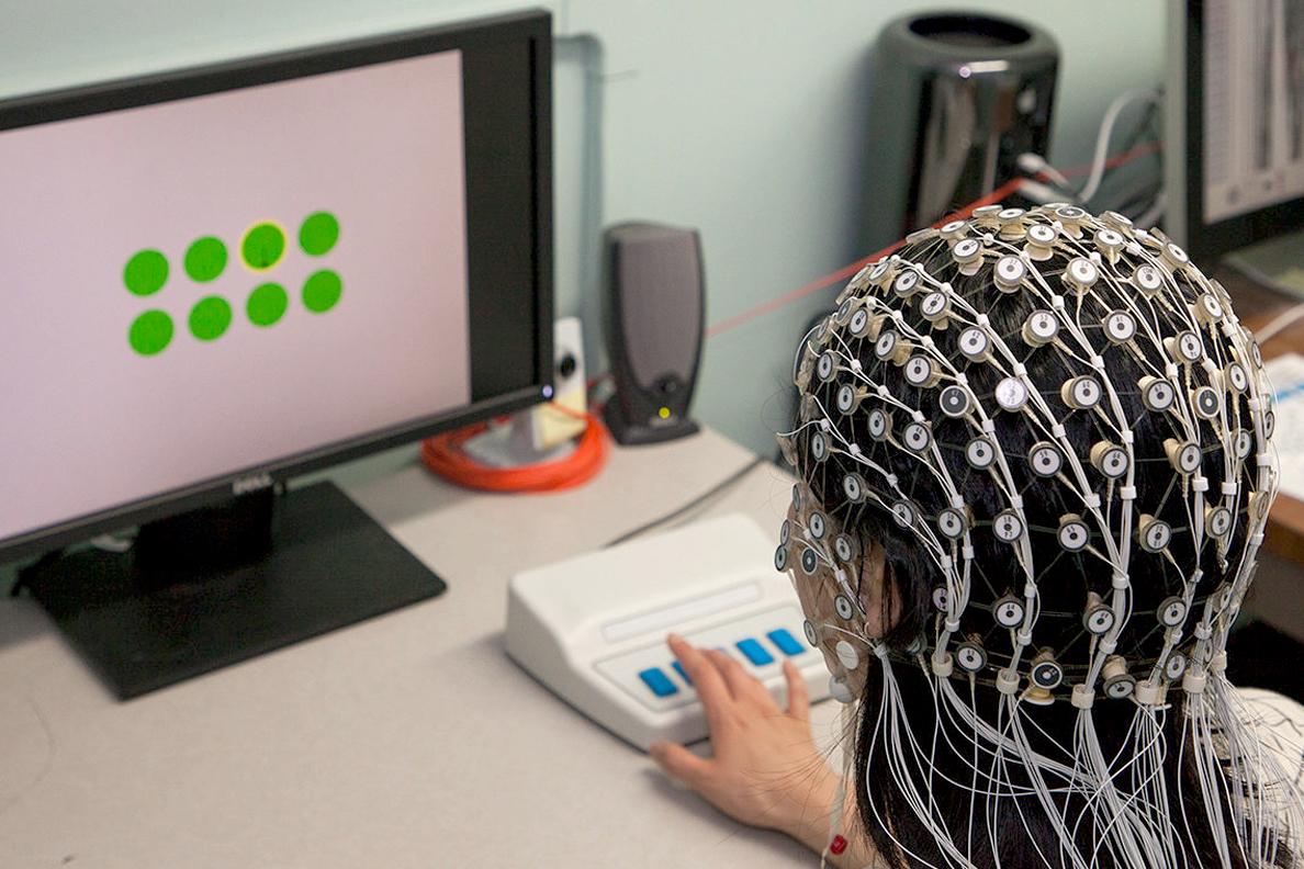 Woman wearing an EEG cap looks at a computer screen.