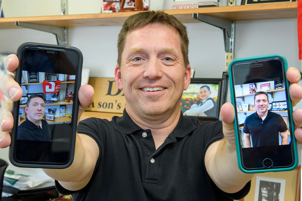 Closeup of Chris Barry holding two phones.