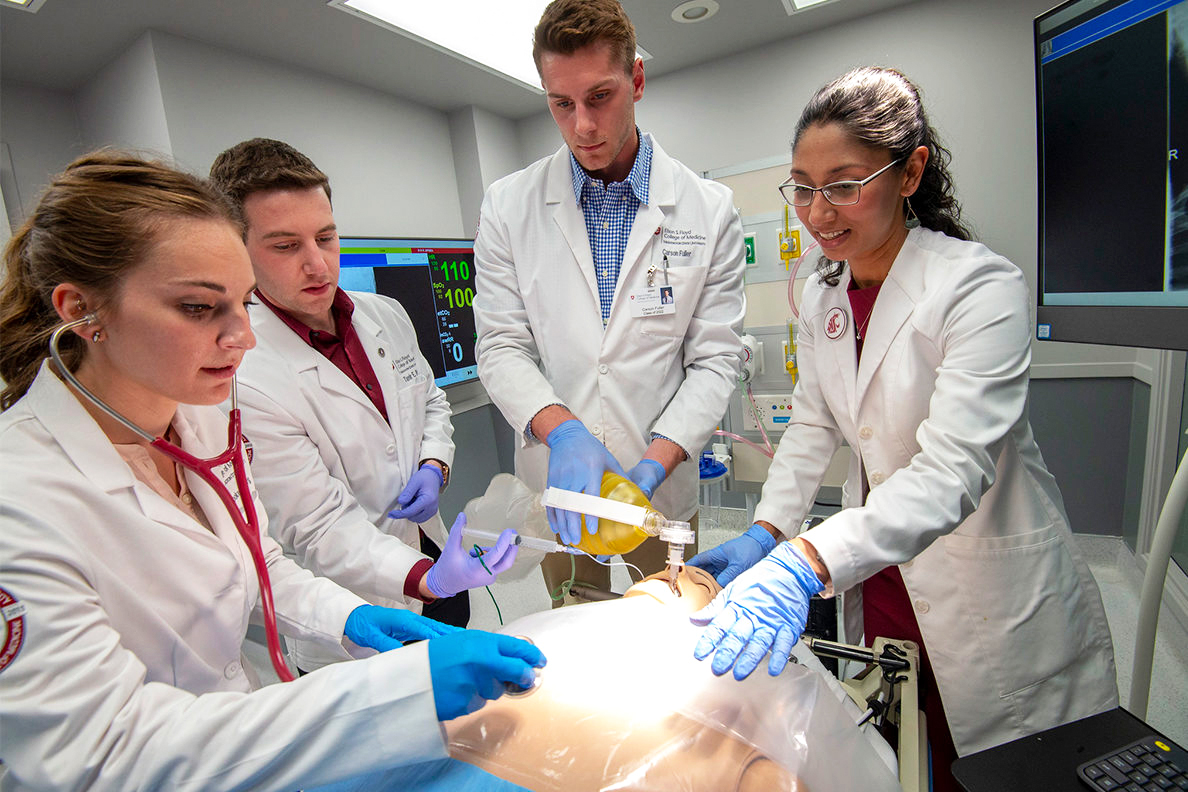 Medical students working with a body simulator.