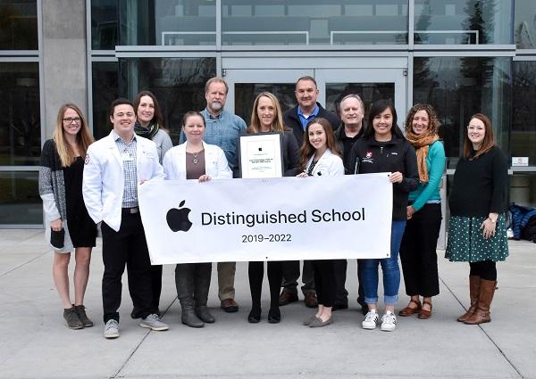group holding Apple Distinguished School banner