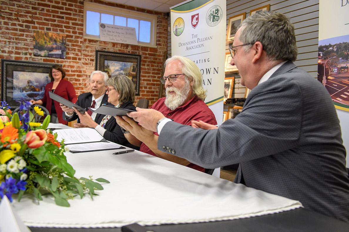 Kirk Schulz and other representatives signing a memorandum of understanding.
