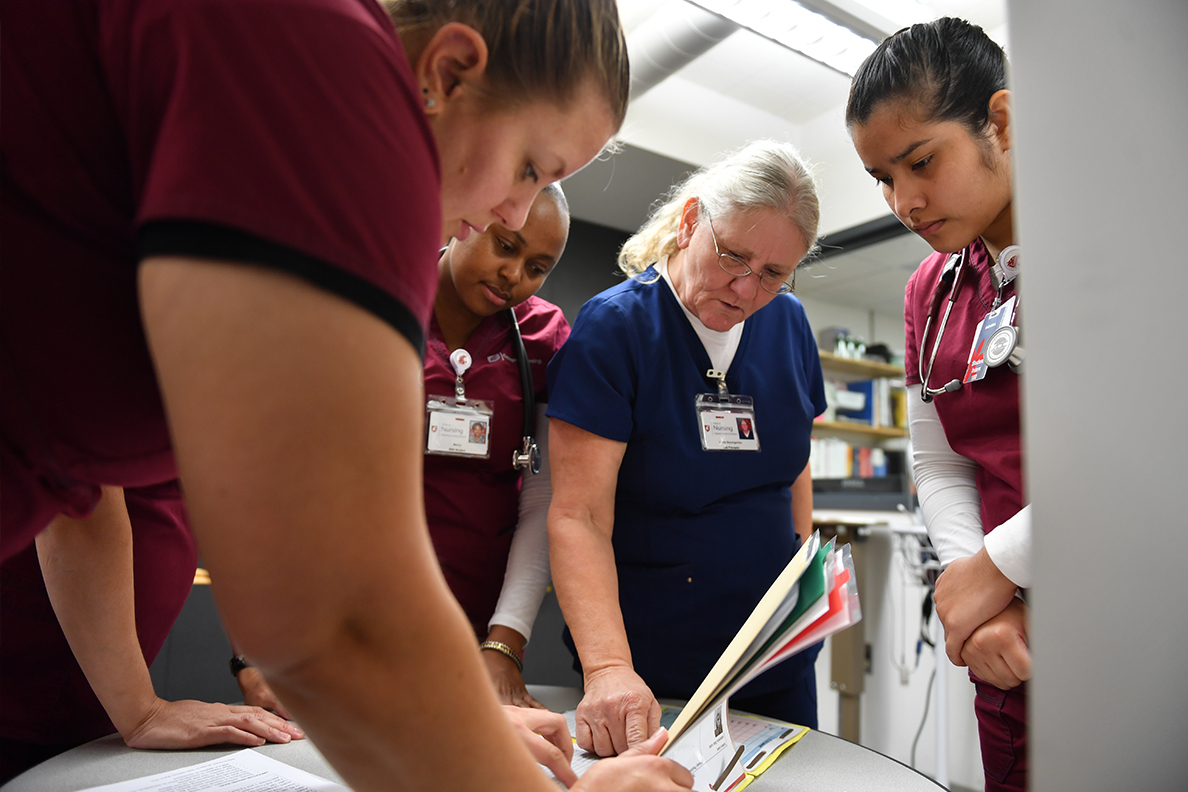 Nursing students look at documents around a table.