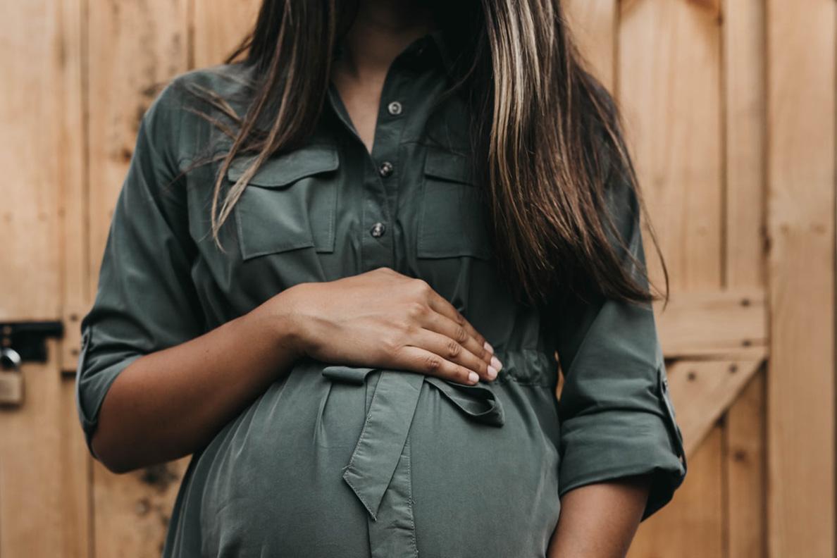 Pregnant woman in green shirt standing before wooden door