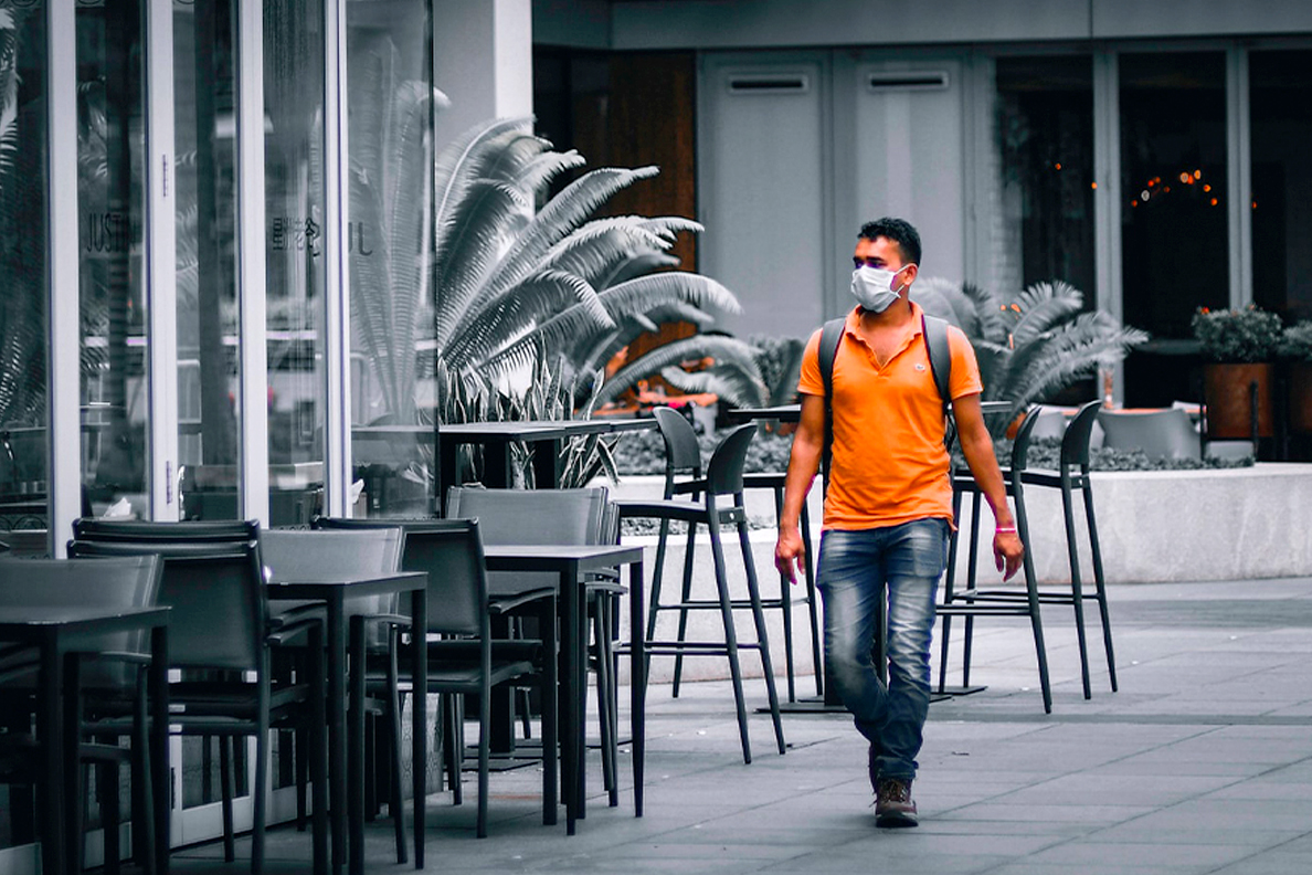 A man wearing a mask walks past closed businesses.