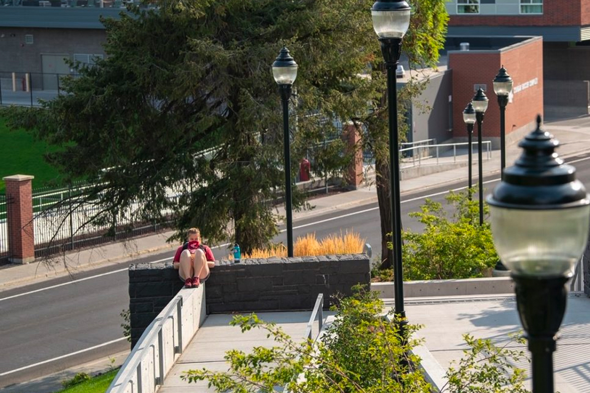 A student sitting alone on the WSU Pullman campus.