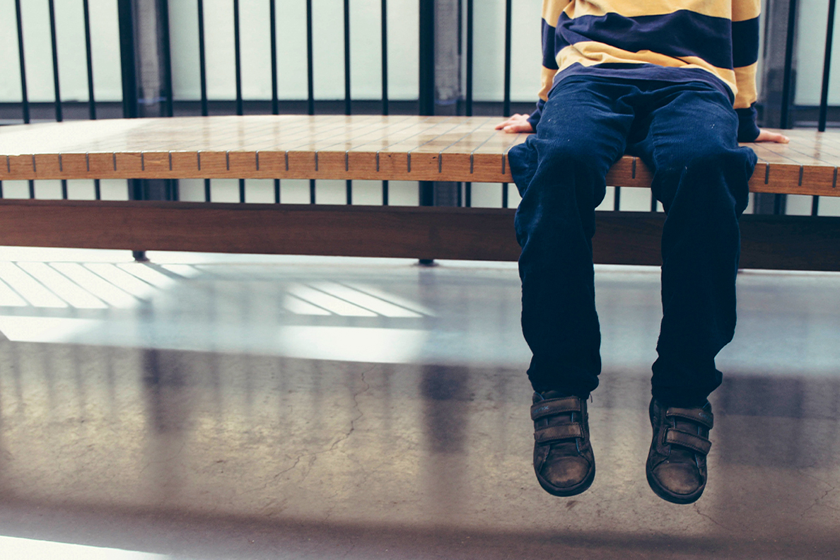 A child's legs dangling off the end of a bench in a juvenile center.
