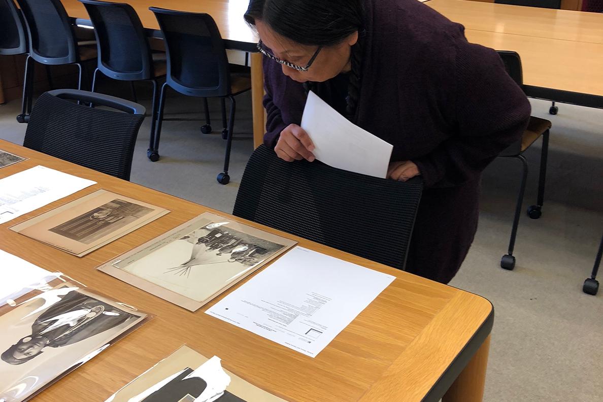 Valerie Switzler views photographs on a table.