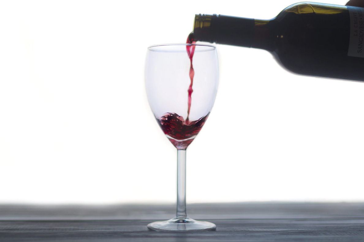 Closeup of someone pouring a glass of red wine.