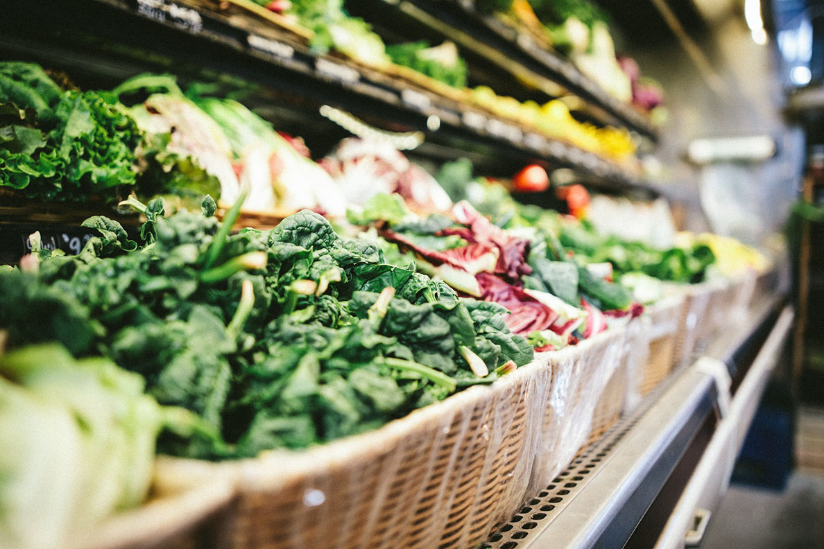 A produce aisle in a grocery store featuring spinach greens and other vegetables.