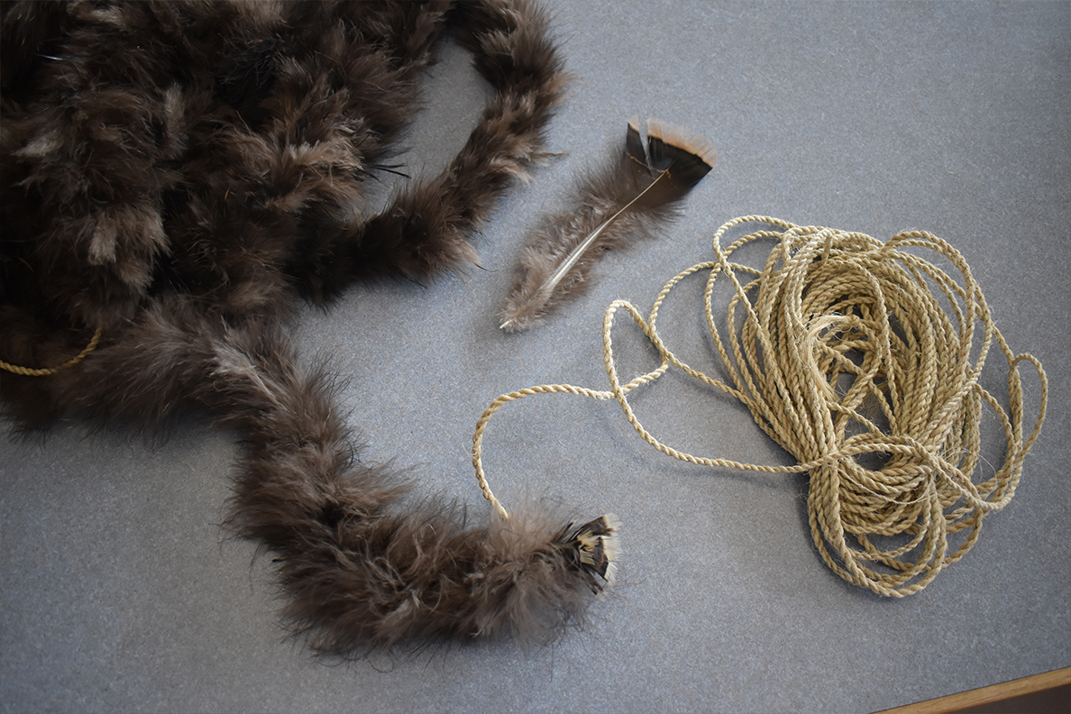 A segment of fiber cord that has been wrapped with turkey feathers, along with a single downy feather.