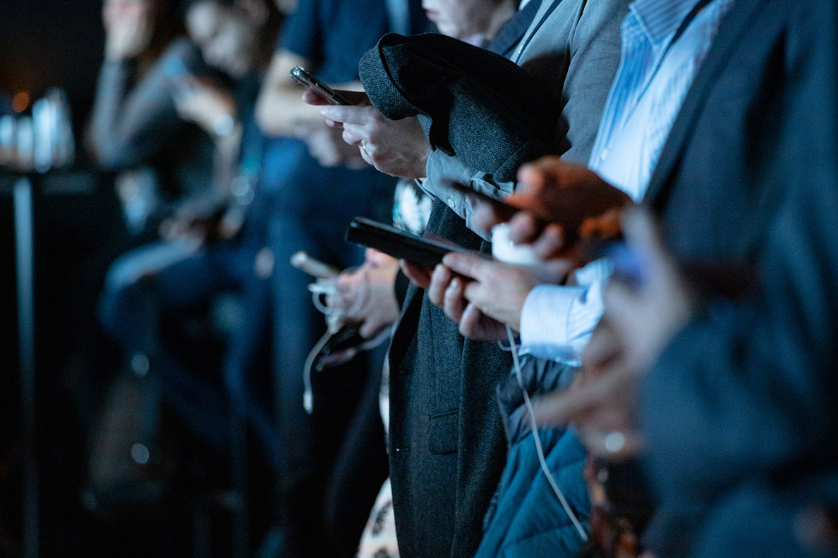 Closeup of a line of people holding their cell phones.