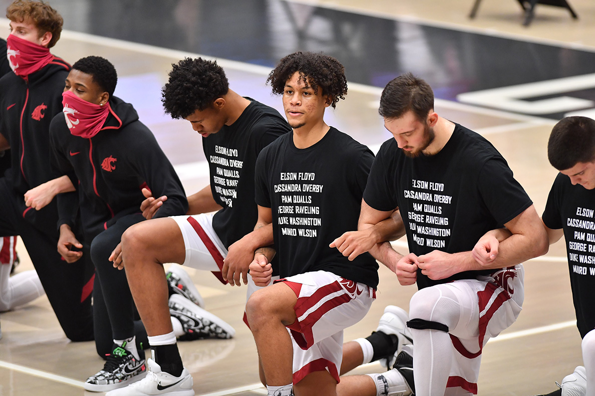 WSU men's basketball team kneeling on court with locked arms.