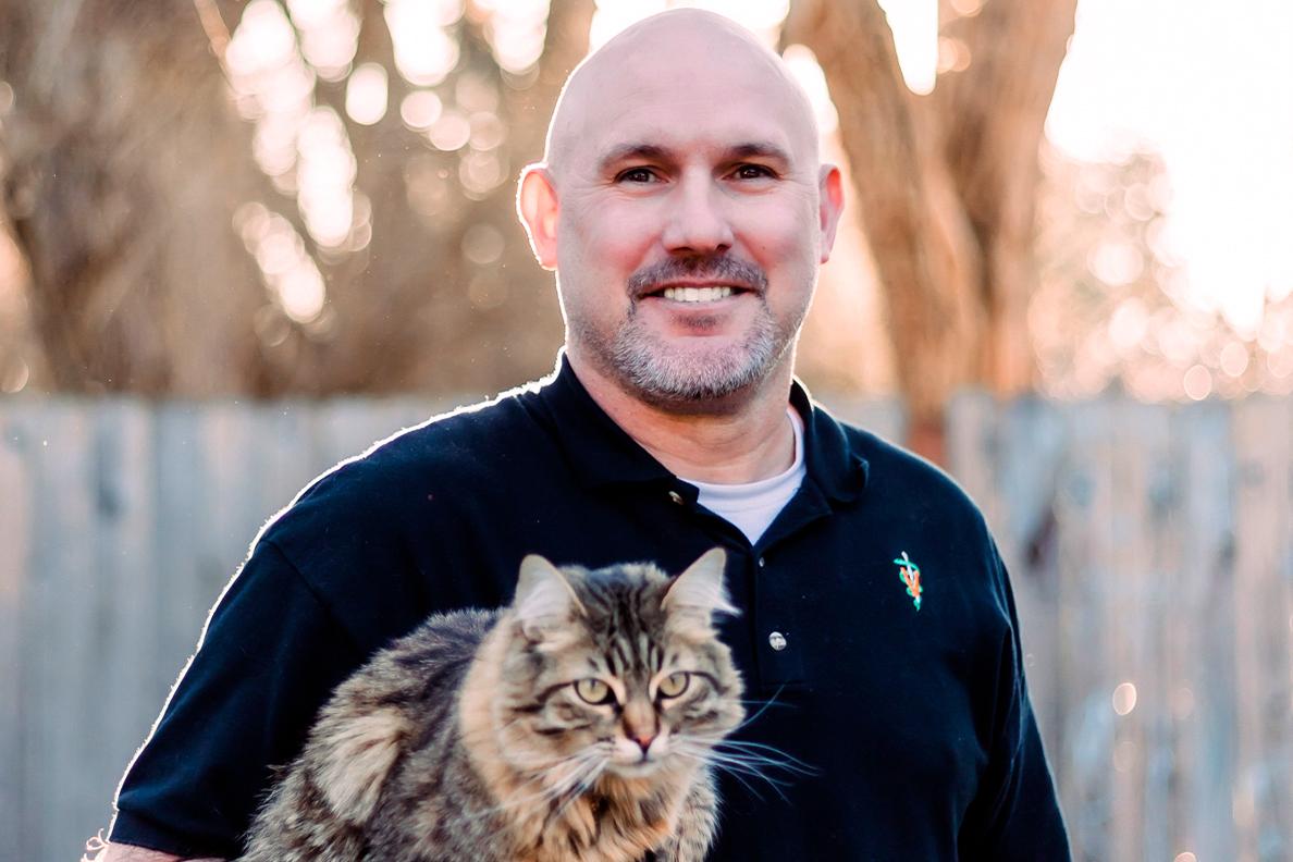 Closeup of Ryan Baumwart holding a cat.