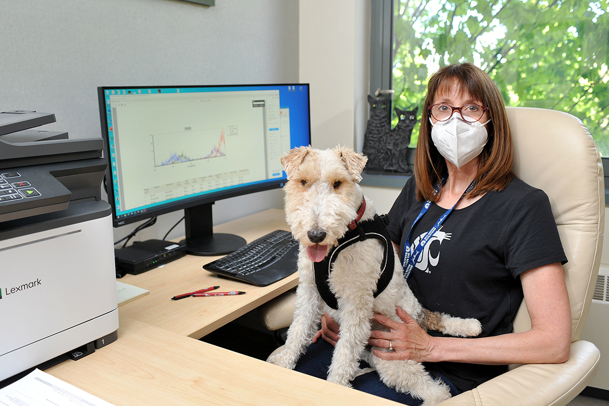 Dr. Katrina Mealey sitting at a desk with her dog, Borghi, on her lap.