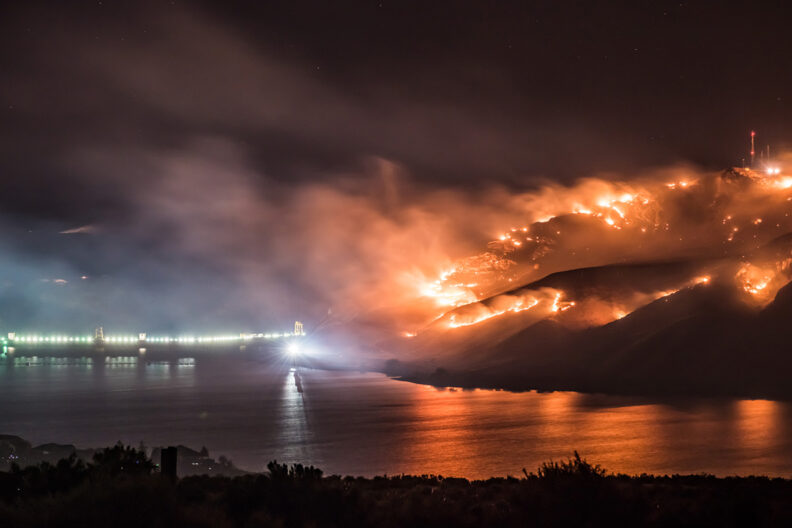 A wildfire burns at night as it approaches a river