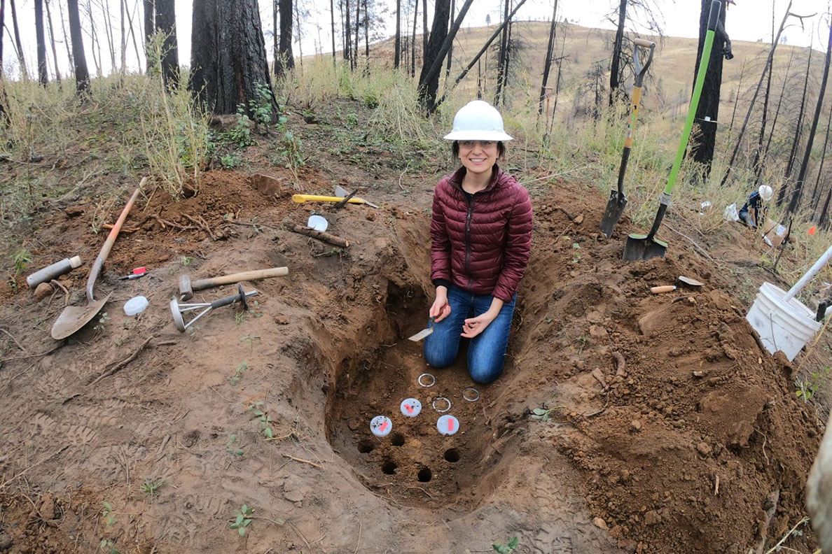 A woman in a hard hat kneeling before a soil pit dug on a burned forest landscape