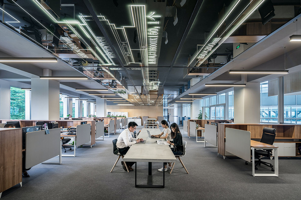 Three workers sitting at a table in an otherwise spacious empty office area.
