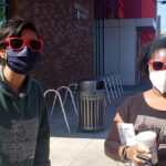 Two WSU Everett students wearing sunglasses and face masks outside.