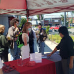 Students, faculty, and staff gathered at an information table located outside on the WSU Everett campus.