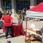 Students, faculty, and staff at information tables located outside on the WSU Everett campus.