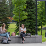 People seated outdoors on the WSU Spokane campus as they eat and socialize.