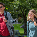 Two WSU Spokane students acknowledging a photographer as they walk across campus.