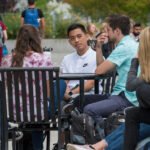 WSU Spokane students seated at an outdoor table talking to one another.
