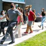 Butch T. Cougar and WSU Tri-Cities faculty, staff, and students dancing outdoors on campus.