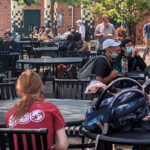 WSU Vancouver students gathered around outdoor tables eating and socializing.