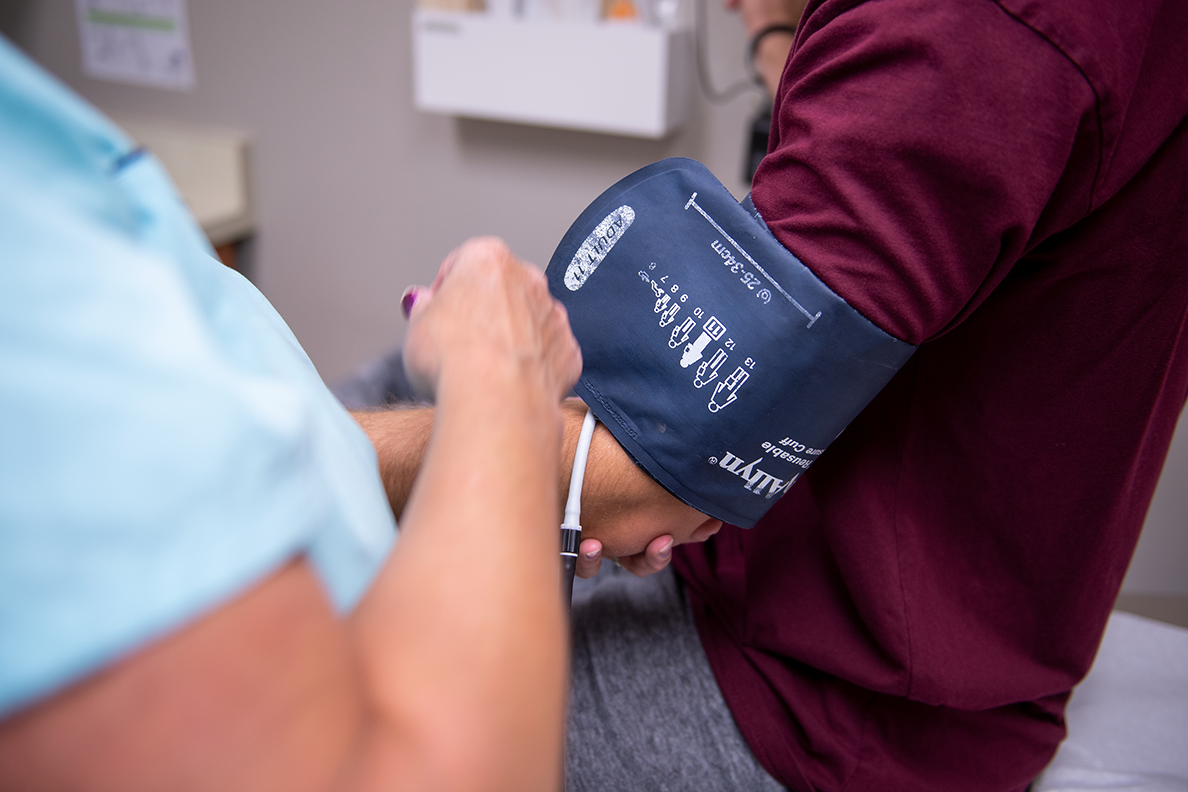 Closeup of someone administering a blood pressure test.