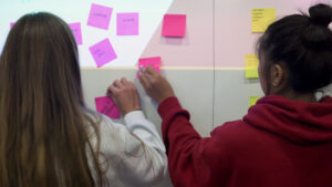 Student-athletes place sticky notes on a whiteboard as part of a class exercise.