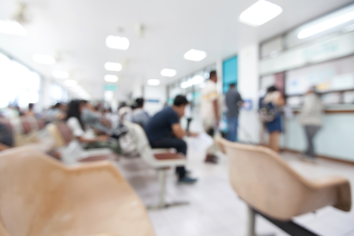 Blurred photo of several patients in a hospital waiting room.