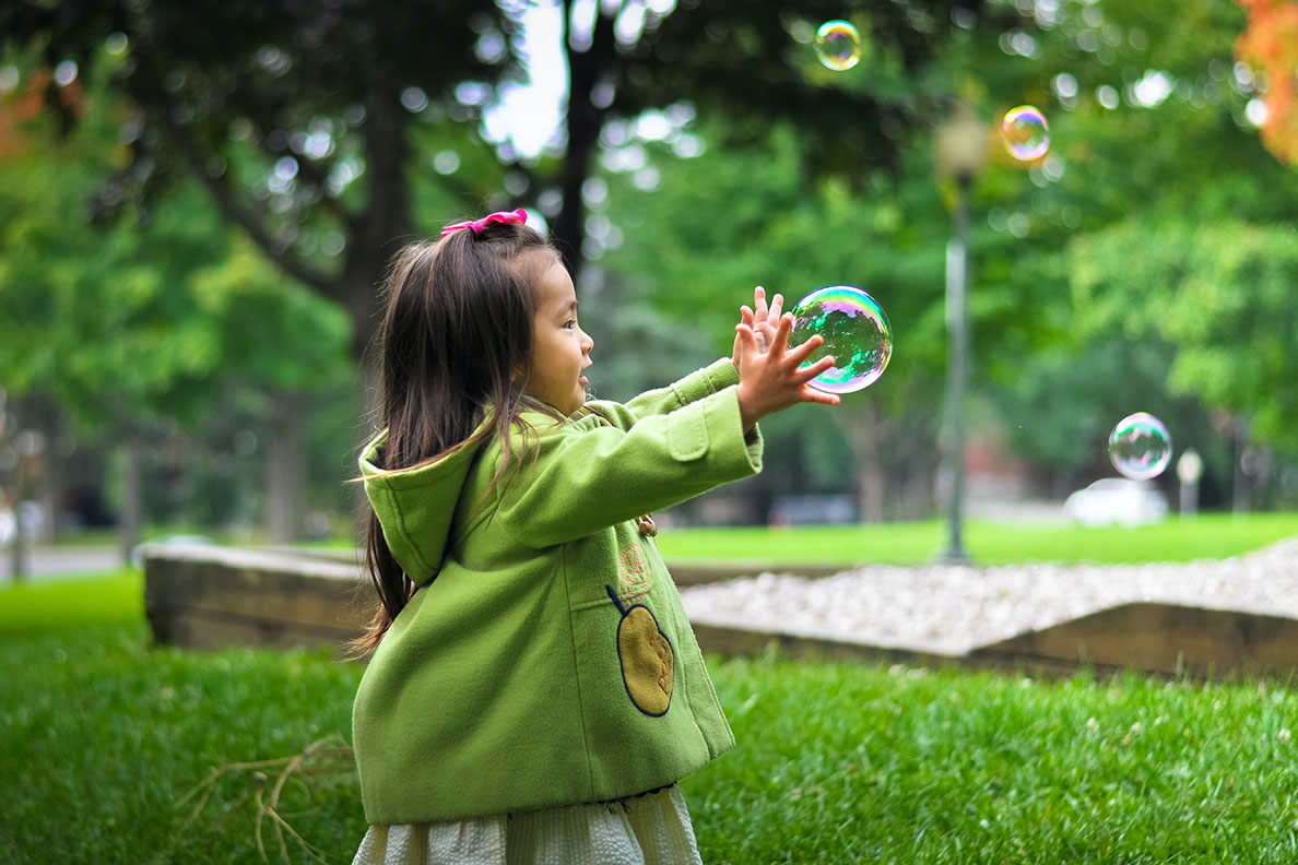 small girl in green coat trying to catch a bubble outside