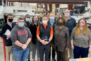 Washington State University and Clemson University students pose together inside a manufacturing facility.