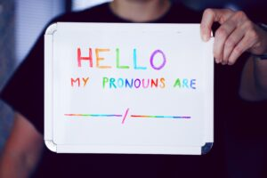 Someone holding a whiteboard sign that reads 'Hello. My pronouns are…'