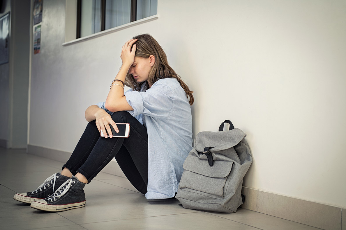 Upset and depressed girl holding smartphone sitting on college campus floor holding head