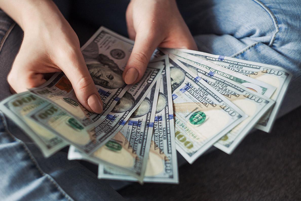 A woman's hands holding a fan of $100 bills