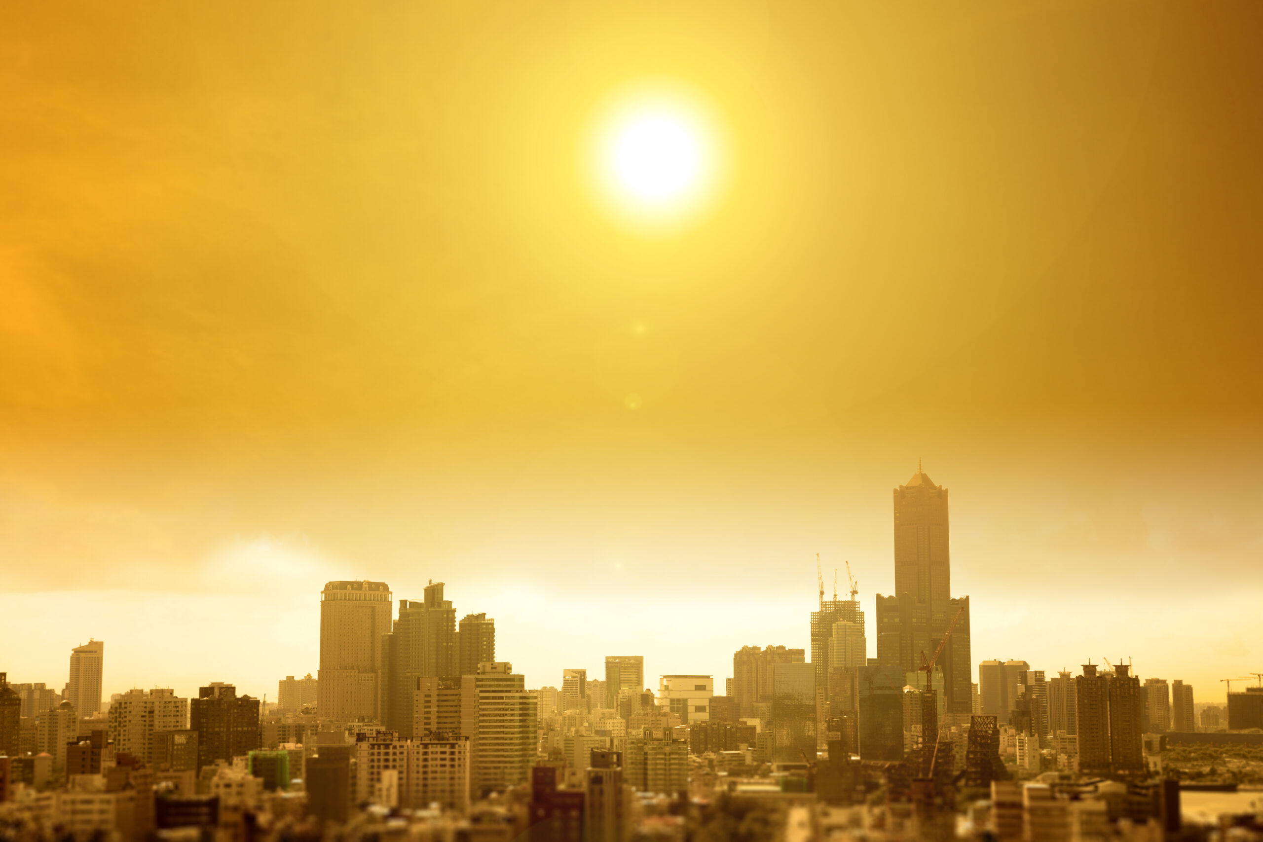The sun shining over a large cityscape on a hot day.